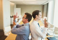 Playful businessmen pretending to duel back to back in conference room Stock Photos
