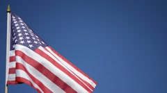 USA hand flag fluttering in the wind against blue skies. Stock Footage