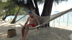 Young man relaxing on hammock on exotic beach Stock Footage