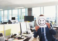 Portrait of businessman holding smiley face printout over his face in office - stock photo