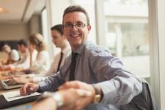 Portrait smiling businessman handshaking in conference room meeting - stock photo