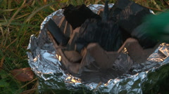 Put charcoal in handmade brazier made of a can of canned food and foil Stock Footage