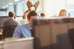 Businessman wearing antler headband in office Stock Photos