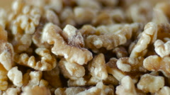 Raw shelled walnuts rotating on a wooden cutting board close up Stock Footage