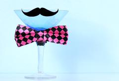 Blue martini glass with mustache and bow tie. - stock photo