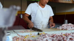 A man chops off the claws from a pile of chicken feet with a large knife Stock Footage