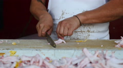 A man removes the ends of chicken feet - med. dolly shot Stock Footage