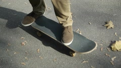 Autumn, fallen leaves on the road, the guy on a skateboard, moving, close-up. Stock Footage