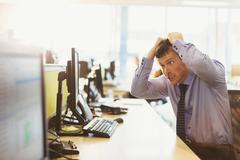 Stressed businessman pulling his hair out at computer in office - stock photo