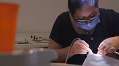 Portrait of a hispanic dentist cleaning a man's teeth - dolly shot Stock Footage