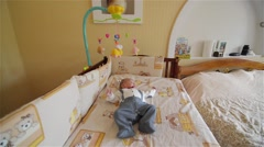 Little cute baby boy lying in crib with toy Stock Footage