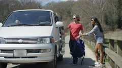 4K Hipster friends going on a road trip, young couple getting into camper van Stock Footage