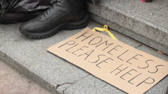 Homeless please help cardboard sign lying on the ground, homeless man begging Stock Footage