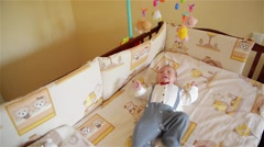 Little cute baby boy lying in crib with toy, boy crying Stock Footage