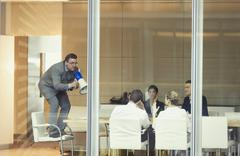 Businessman with megaphone on top of chair in conference room meeting - stock photo