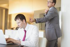 Angry businessman aiming rubber band at unsuspecting businessman working at Stock Photos