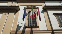 University, Italian and European flags waving above the entrance of Pavia Stock Footage
