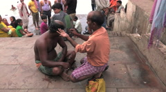 A man having his head shaved by a hairdresser on the ghats, steps by the Ganges. Stock Footage