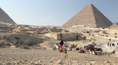 Man riding camel in desert landscape in front of the pyramids at Giza - stock footage
