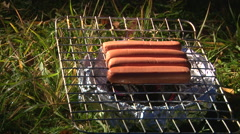 Take Sausages out of brazier bbq grille Stock Footage