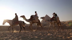 Egyptian man riding a horse and leading tourists on a camel at pyramids of Giza - stock footage