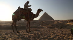 Egyptian man sitting on a camel at pyramids of Giza - stock footage