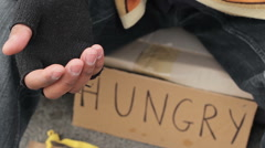 Homeless person begging with outstretched trembling hand, poverty and misery Stock Footage