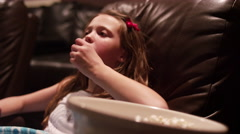 A young girl watching a movie in a home theater with popcorn Stock Footage
