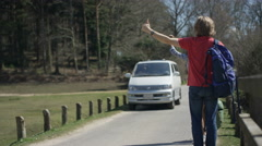 4K Hipster couple hitchhiking on the road, camper van pulls over to pick them up Stock Footage