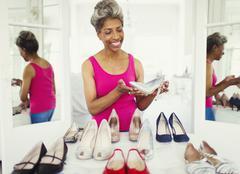 Smiling mature woman looking at high heels in closet Stock Photos