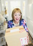 Surprised mature woman receiving package - stock photo