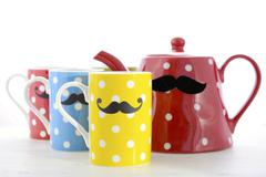 Colorful coffee mugs with mustaches. - stock photo