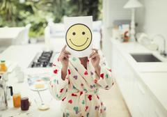 Portrait of women holding smiley face printout over face in kitchen Stock Photos