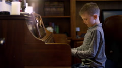Little boy at home playing the piano Stock Footage