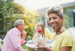 Portrait smiling mature woman enjoying lunch with friends in garden Stock Photos