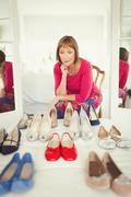 Indecisive mature woman deciding which shoes to wear in closet - stock photo