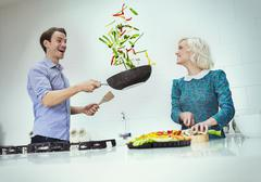 Surprised couple cooking flipping vegetables in skillet in kitchen Stock Photos
