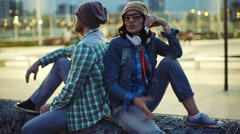 Couple of hipsters sitting at night in the city and talking on cellphone Stock Footage