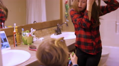A young girl does her hair in the bathroom Stock Footage