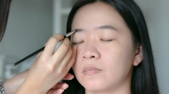 Woman is doing facial cosmetic makeup using eyebrow brush to a model Stock Footage