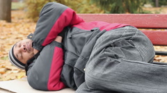 Vagabond in jacket and jeans sleeping on bench, trying to keep warm, poverty Stock Footage