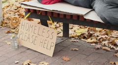 Man dressed in old clothes sleeping on bench in park with homeless help sign Stock Footage