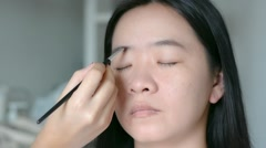 Woman is doing facial cosmetic makeup using eyebrow brush to a model - stock footage