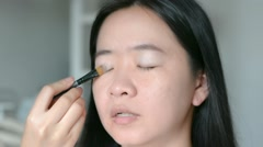 Woman is doing facial cosmetic makeup using eyelid brush to a model Stock Footage