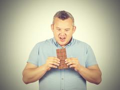 Fat man wants to take a bite of chocolate. Stock Photos