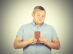 Fat man refuses to chocolate. Stock Photos