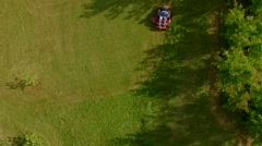 Elevated view of man cutting grass on a riding lawn mower Stock Footage