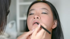 Woman is doing lips cosmetic makeup using pink lipstick brush to a model Arkistovideo