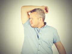 Fat man, smelling sniffing his armpit, something stinks bad, foul odor Stock Photos