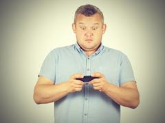 fat man looks at the phone. - stock photo